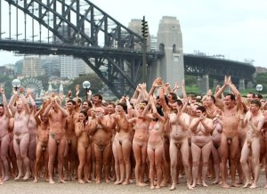 "SYDNEY, AUSTRALIA - MARCH 01: (EDITORS NOTE: Image contains nudity.)Nude members of the public applaud as they notice television reporter Grant Denyer stripping off to take part in ""Mardi Gras: The Base"", an art installation by artist Spencer Tunick, at the Sydney Opera House on March 1, 2010 in Sydney, Australia. More than 5000 people gathered on a cool, cloudy Sydney morning for Tunick's first Australian installation, which follows visits to the US, Brazil, France, England and Austria. Tunick stated that the title of the work, commissioned by the Sydney Gay and Lesbian Mardi Gras, refers to the sameness of individuals, regardless of their sexual preferences. (Photo by Don Arnold/WireImage)"